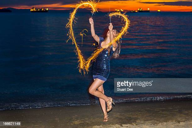 Woman with sparklers at beach