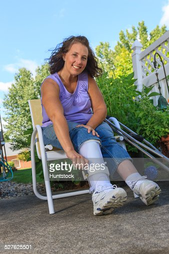 Woman With Spina Bifida Adjusting Leg Brace So She Can Walk High-res Stock Photo