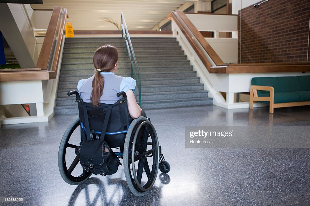 Woman with Spina Bifida in wheelchair studying difficulty of accessing stairway : Stock Photo