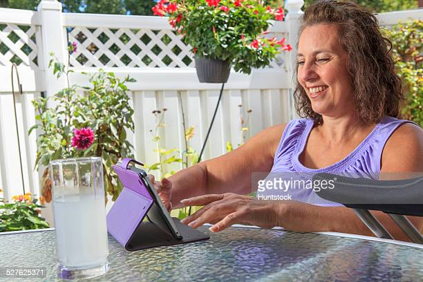 Woman with Spina Bifida on patio working on tablet