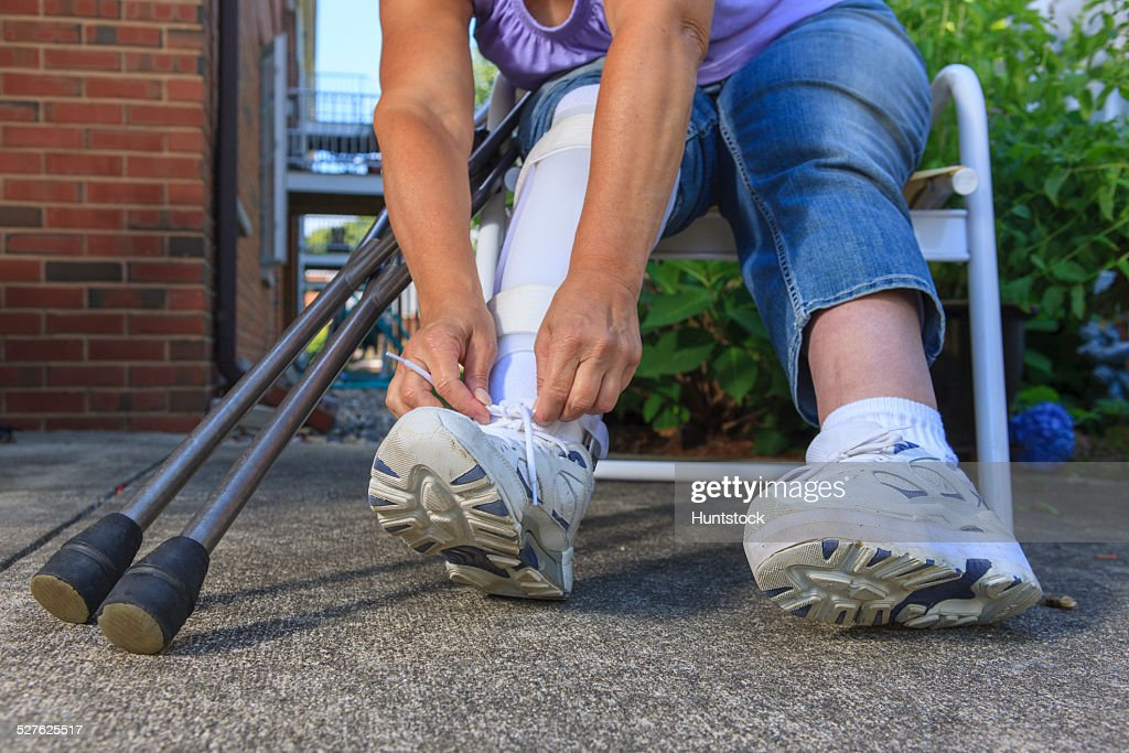 Woman With Spina Bifida Tying The Shoe On Leg Brace Photo - Getty Images