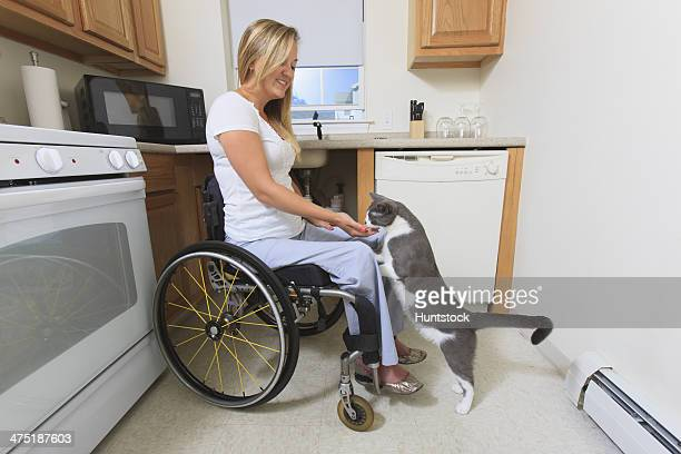 Woman with spinal cord injury in her accessible kitchen feeding her cat