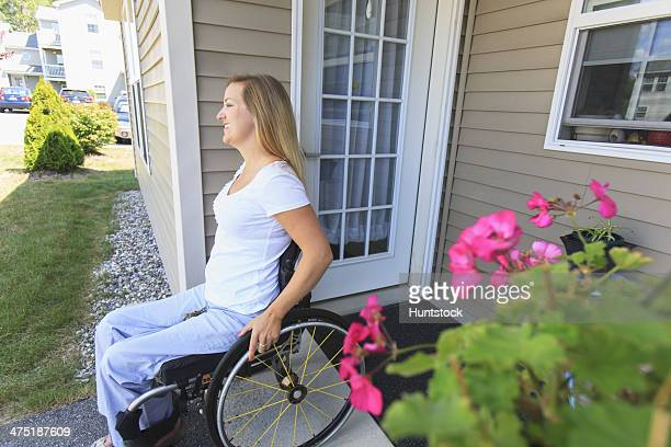 Woman with spinal cord injury in wheelchair leaving her house