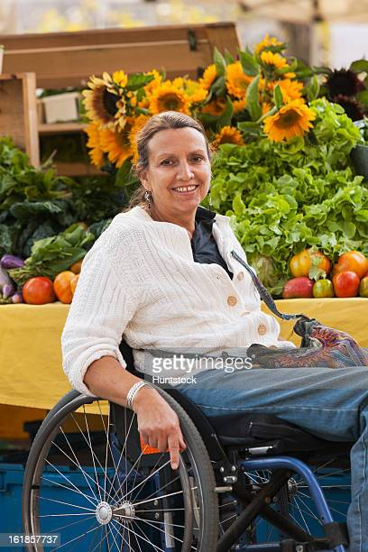 woman with spinal cord injury in wheelchair shopping at outdoor market - paraplegic stock photos and pictures