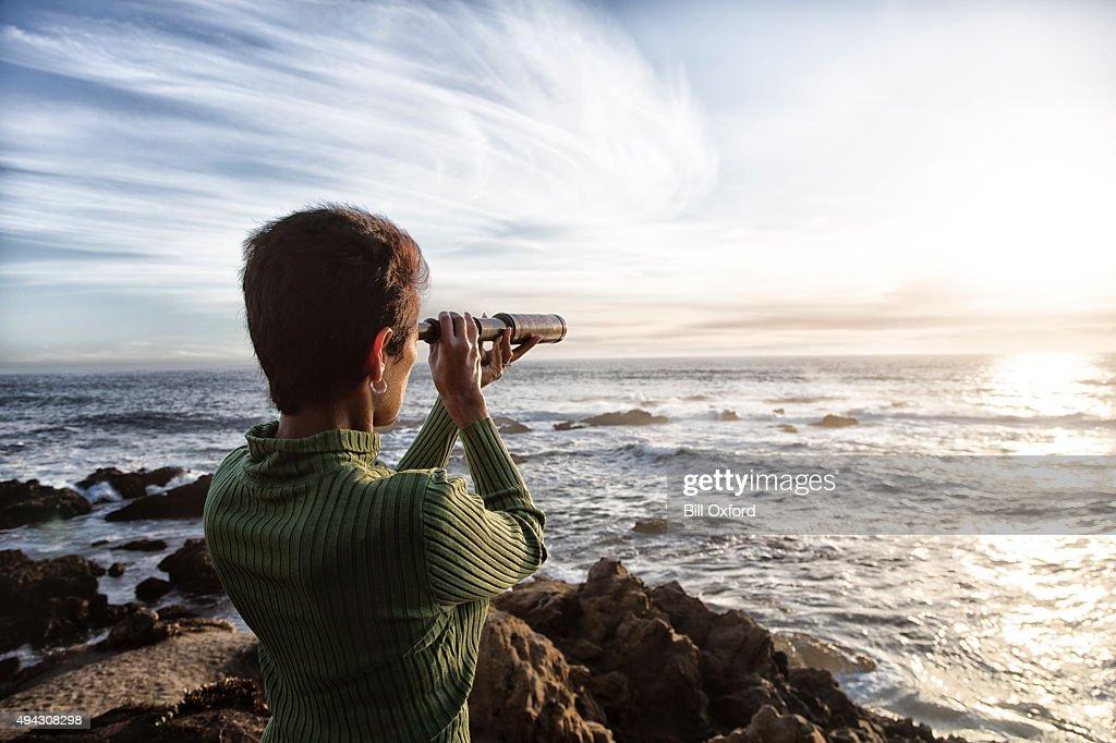 Mulher com uma luneta olhando para o mar : Foto de stock