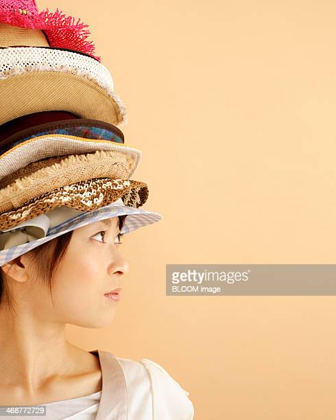 Woman With Stack Of Hats On Head