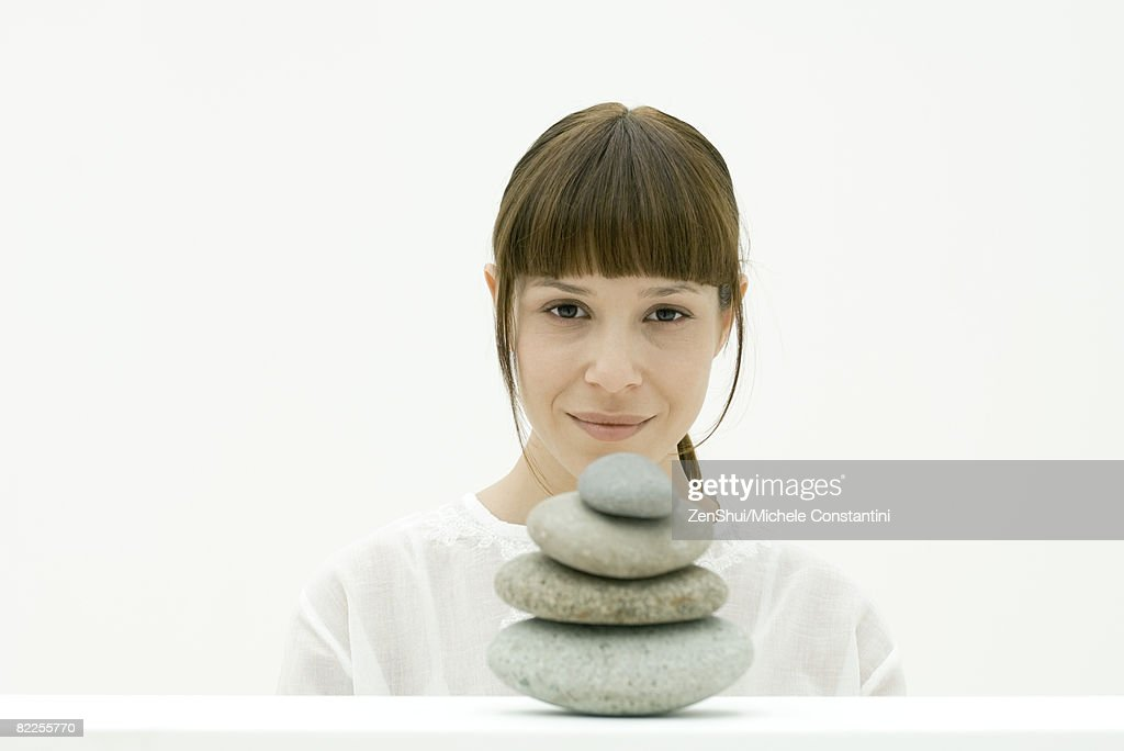 Woman with stack of stones, portrait : Stock Photo
