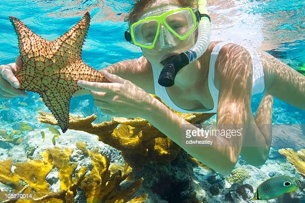 Mujer con estrella de buceo en el Caribe