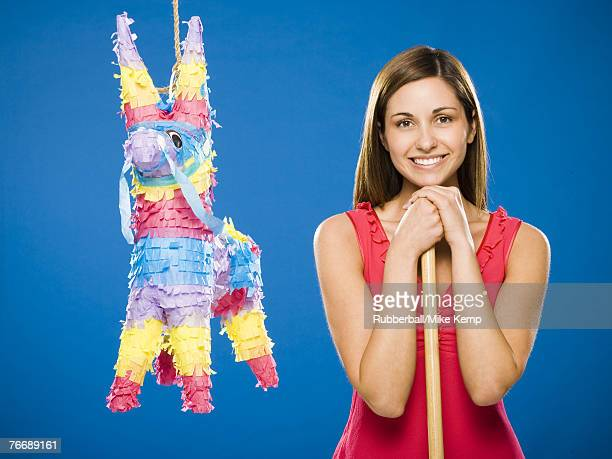 Woman with stick standing beside pinata smiling