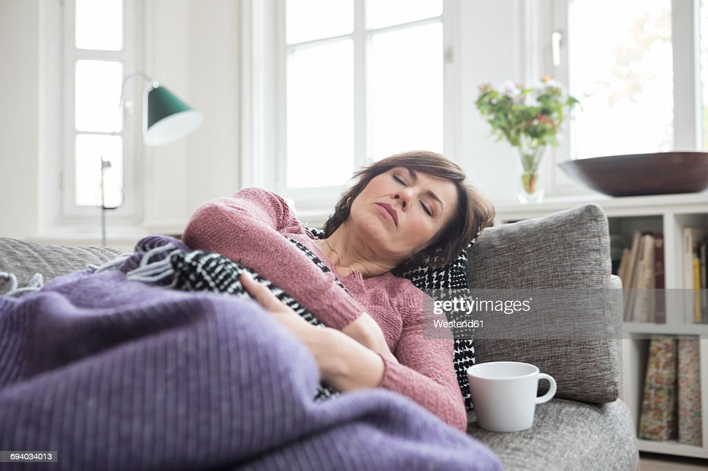 Woman with stomach ache lying on the sofa : Stockfoto
