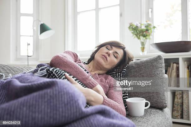 woman with stomach ache lying on the sofa - krankheit stock-fotos und bilder