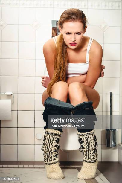 woman with stomachache sitting on toilet bowl in bathroom - femme wc photos et images de collection