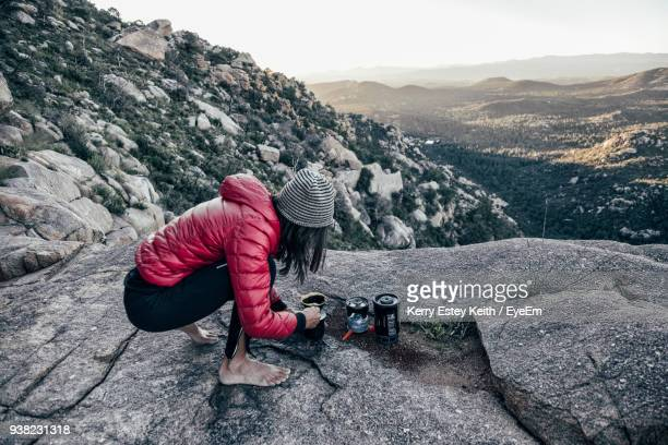 woman with stove crouching on mountains against sky - kerry estey keith stock photos and pictures
