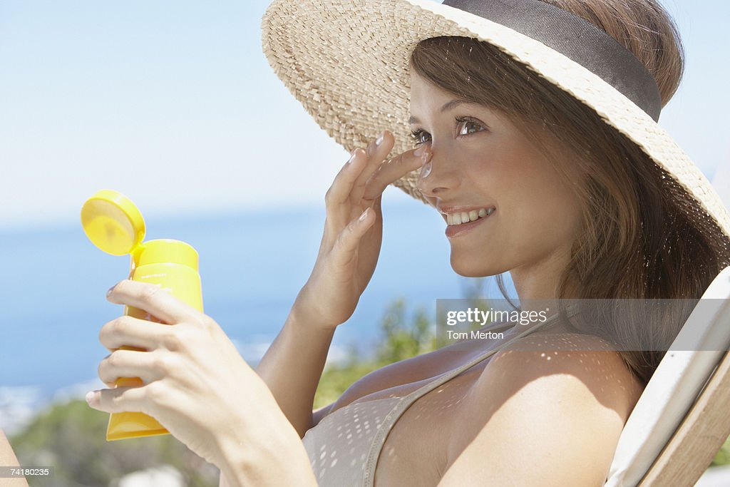 Woman with straw hat applying sun block to face outdoors : Stock Photo