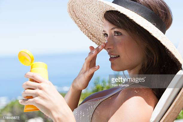 woman with straw hat applying sunblock to face outdoors - sunscreen stock photos and pictures