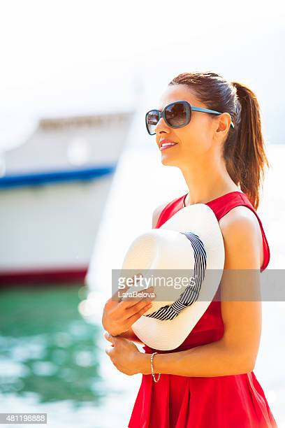Woman with straw hat at harbor