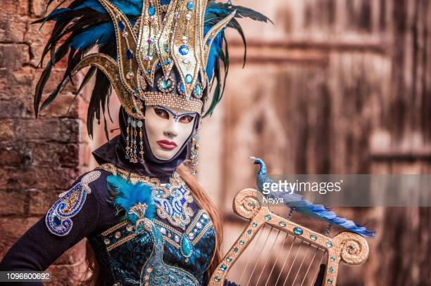woman with string instrument wearing attractive golden and blue costume at venice carnival - venice carnival stock pictures, royalty-free photos & images