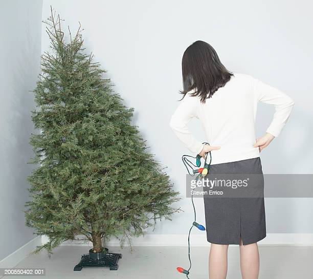 Woman with string of lights looking at bare Christmas tree, rear view