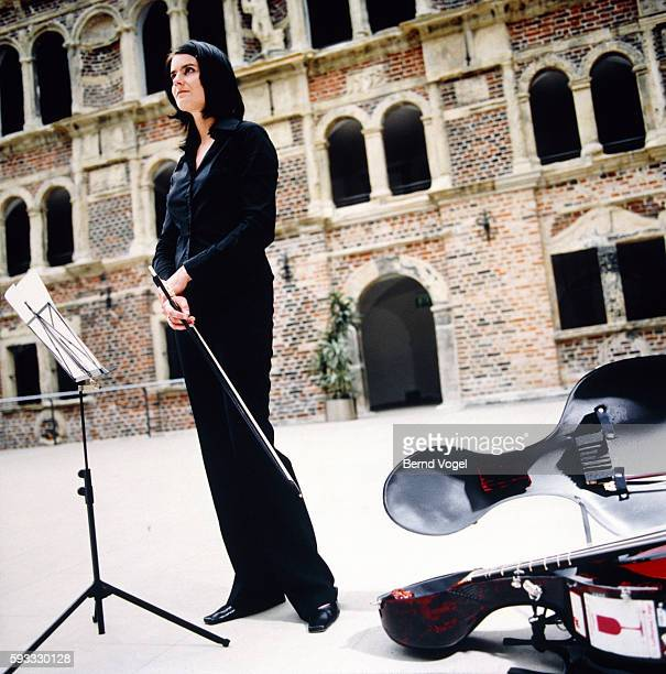 Woman with stringed instrument before music stand