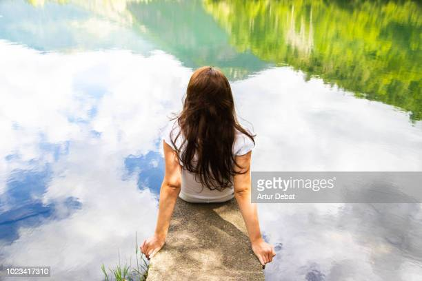 Woman with stunning mountain landscape reflected in the lake water.