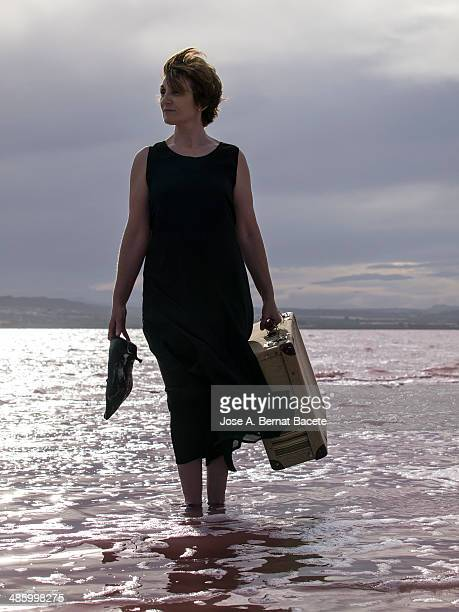 Woman with suitcase and heels in the hand