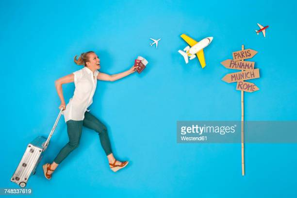 Woman with suitcase hurrying to to get her flight for a city break