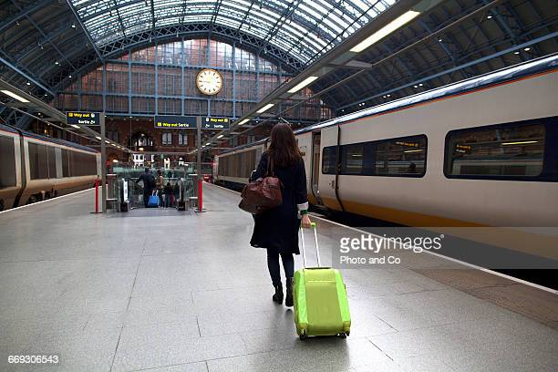 Woman with suitcase in a train station