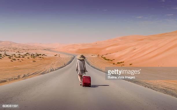 woman with suitcase in an empty road in the desert - paisajes de emiratos arabes fotografías e imágenes de stock