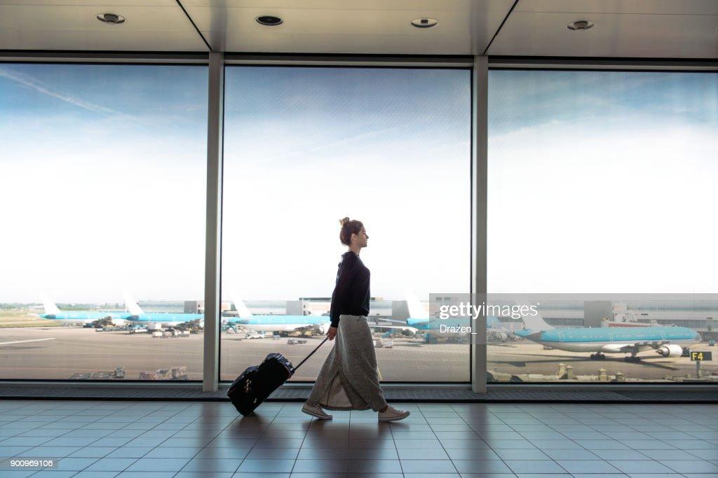 Mulher com mala vai para embarcar no próximo voo : Foto de stock