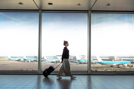 Woman with suitcase is going to board on the next flight - gettyimageskorea