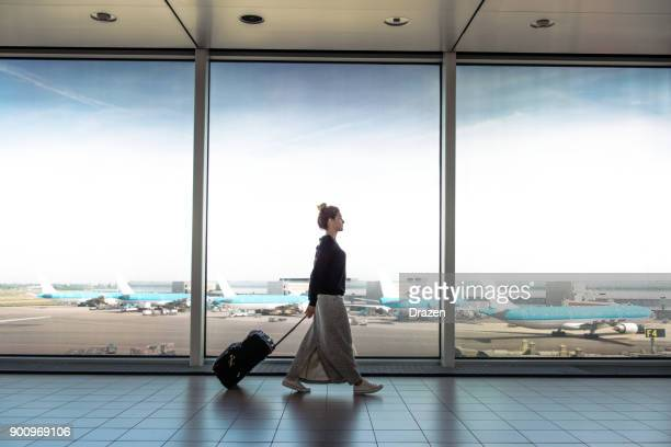 woman with suitcase is going to board on the next flight - passageiro imagens e fotografias de stock