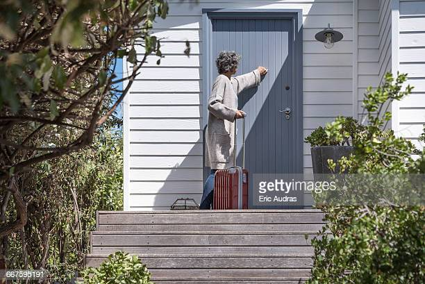 woman with suitcase knocking on door - knocking on door stock photos and pictures