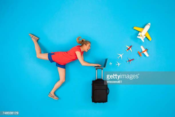 Woman with suitcase looking at laptop with airplanes coming out
