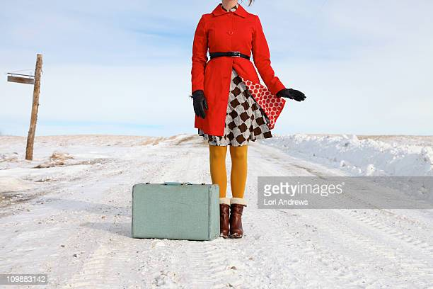 Woman with suitcase on snowy road