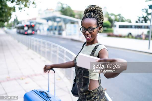 Woman with suitcase taking selfie