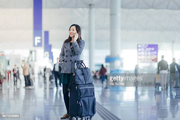 Woman with suitcase using smartphone in airport