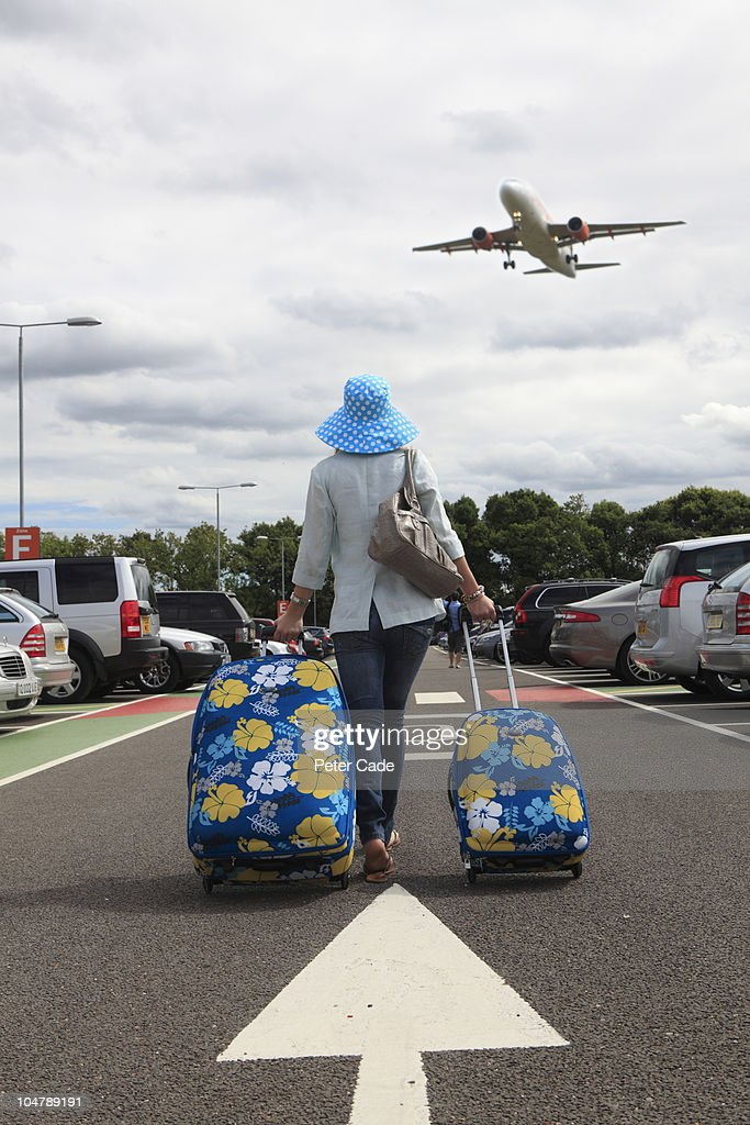 Woman with suitcases in airport car park : Foto de stock