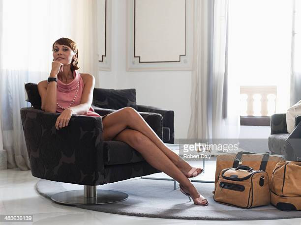 woman with suitcases sitting in waiting area - beautiful dominant women stock pictures, royalty-free photos & images