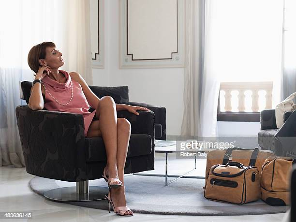 woman with suitcases sitting in waiting area - 50 59 years stock pictures, royalty-free photos & images