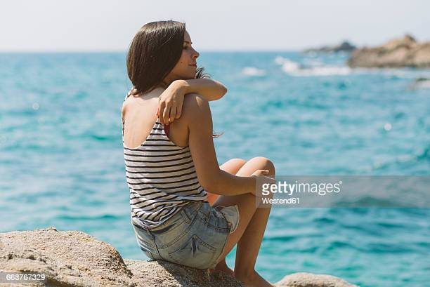 Woman with summer clothes looking out to sea on the beach of Blanes