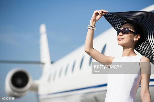 Woman with Sun Hat by Airplane