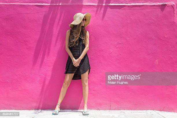 Woman with sun hat on leaning against wall