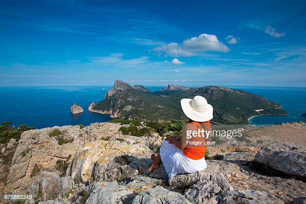 Woman with sun hat overlooks Cap de Formentor