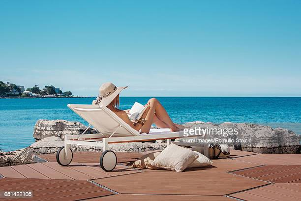 Woman with sun hat relaxing on beach terrace