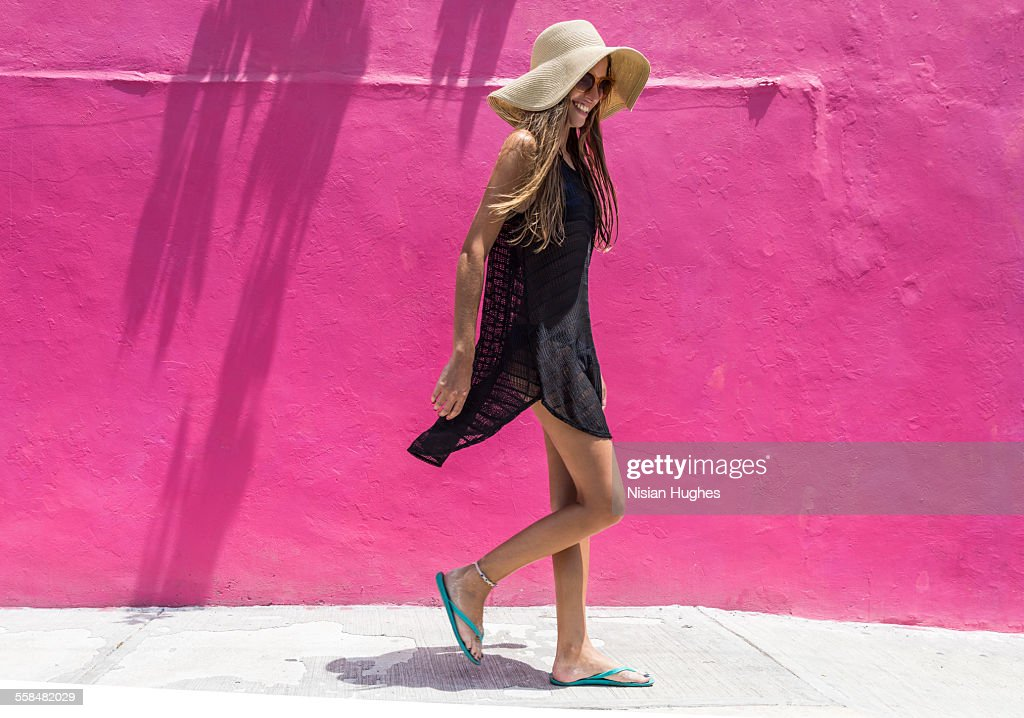 Woman with sun hat walking against bright wall : Stock Photo