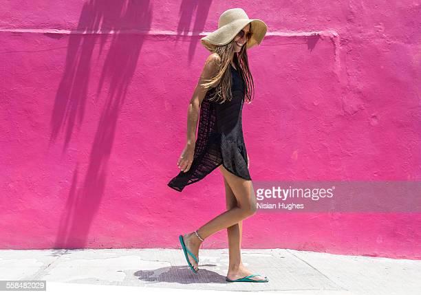 woman with sun hat walking against bright wall - ciabatta infradito foto e immagini stock