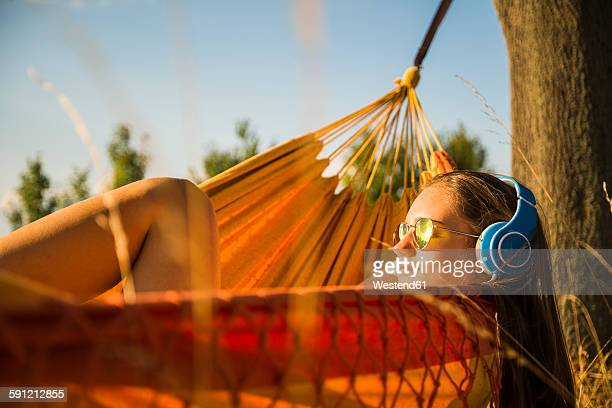 Woman with sunglasses and headphones relaxing in a hammock