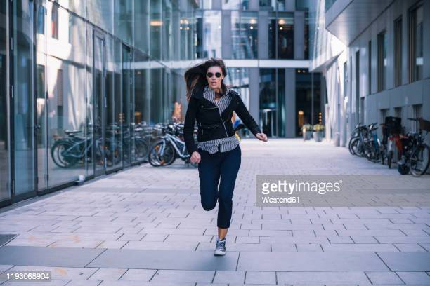 woman with sunglasses running away - escaping stock pictures, royalty-free photos & images