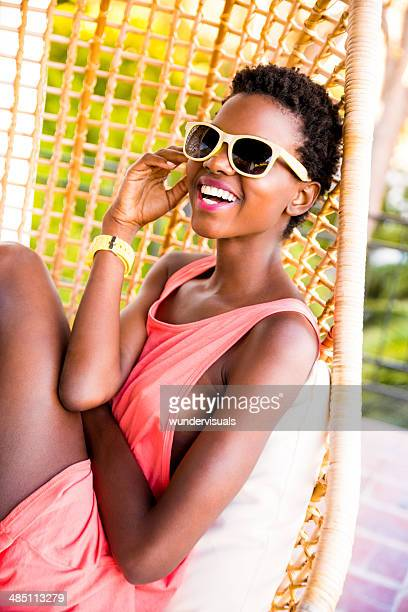 Woman with sunglasses sitting in hanging chair