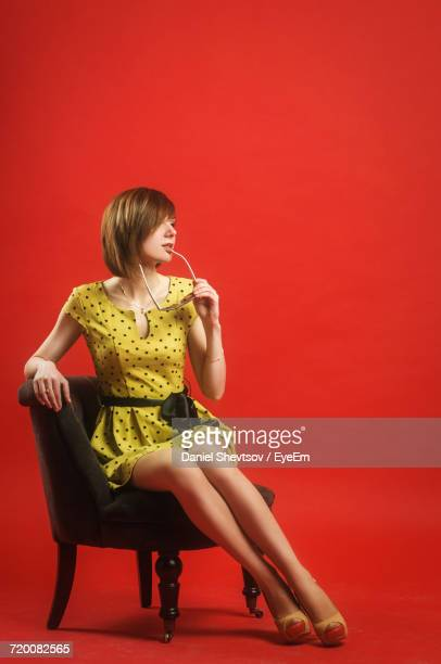 Woman With Sunglasses Sitting On Chair Against Red Background
